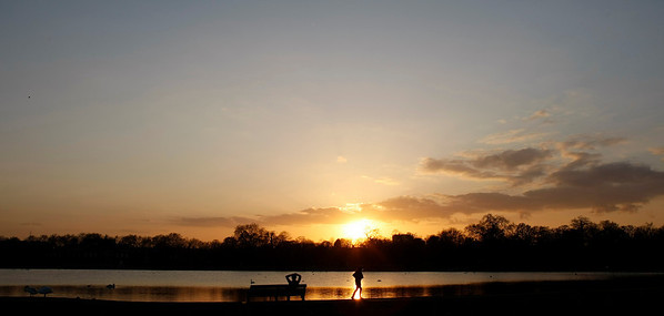 A jogger runs past a man watching the sunset in London's Kensington Gardens, Friday, April, 16, 2010. There are aeroplane-free skies Friday as most of Britain's airports remain closed due to a cloud of volcanic ash in the upper atmosphere above much of Europe, emanating from a volcanic eruption near the Eyjafjallajokull glacier in Iceland. The volcanic ash is a hazard to jet aircraft engines, causing the cancellation of many flights over European airspace.(AP Photo/Alastair Grant)