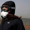 A woman wears a mask and goggles to protect herself from ash caused by volcanic activity Friday April 16 2010, some 120km east of the capital Rejkavik, Iceland. The Eyjafjallajokull  glacier volcano began erupting for the second time in a month on Wednesday, sending ash several miles (kilometers) into the air. Authorities told people in the area with respiratory problems to stay indoors, and advised everyone to wear masks and protective goggles outside. (AP Photo/Brynjar Gauti )