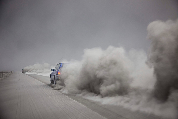 A car is seen driving through the ash from the volcano eruption under the Eyjafjallajokull glacier in Iceland, Friday April 16, 2010. The volcano erupted for the second time in less than a month, melting ice, shooting smoke and steam into the air. Flights around the world have been canceled and passengers stranded as the ash cloud from the volcano affected operations at some of the world's busiest airports. (AP Photo/Omar Oskarsson)