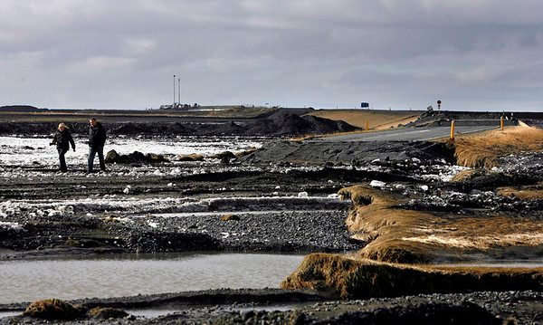 People walk near a section of Iceland's coastal ring road  damaged by floodwaters caused by volcanic activity on the Markarfljot river  Friday April 16 2010, some 120km east of the capital Rejkavik, Iceland. The Eyjafjallajokull  glacier volcano began erupting for the second time in a month on Wednesday, sending ash several miles (kilometers) into the air. Winds pushed the plume south and east across Britain, Ireland, Scandinavia and into the heart of Europe causing travel chaos. (AP Photo/Brynjar Gauti )