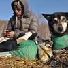 Quinn Iten, of Kotzebue, Alaska  puts booties on his his dog Beavis while his other dog, Gray, is ready to go at the Takotna, Alaska  checkpoint  on Thursday March 11, 2010 during the Iditarod Trail Sled Dog Race. (AP Photo/Anchorage Daily News, Bob Hallinen)