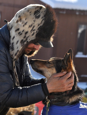 Musher Lance Mackey rubs the head of Rev after rubbing ointment onto one of the dog's front legs at the Takotna, Alaska, checkpoint on Wednesday, March 10, 2010, during the Iditarod Trail Sled Dog Race. (AP Photo/Anchorage Daily News, Bob Hallinen)