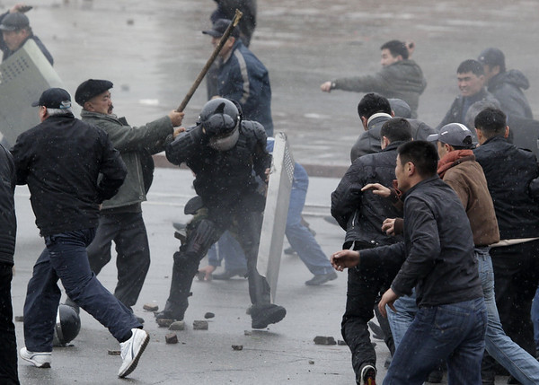 A protestor attacks a Kyrgyz police officer during clashes near the main government buildings in Bishkek, Kyrgyzstan, Wednesday, April 7, 2010. Police in Kyrgyzstan opened fire on thousands of angry protesters who tried to seize the main government building amid rioting in the capital as protests spread across the Central Asian nation. (AP Photo/Ivan Sekretarev)
