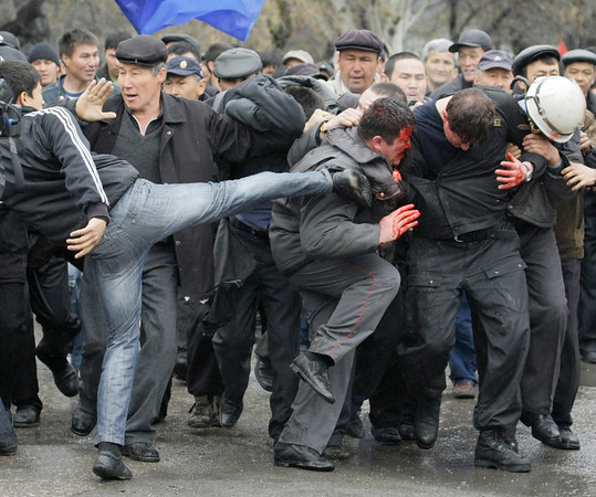 A Kyrgyz protester kicks out at captured police officers at the opposition headquarters in Bishkek, Kyrgyzstan, Wednesday, April 7, 2010. Police in Kyrgyzstan opened fire on thousands of angry protesters who tried to seize the main government building amid rioting in the capital as protests spread across the Central Asian nation. (AP Photo/Ivan Sekretarev)