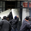 Kyrgyz riot police retreat into a building, as they come under attack from protestors in Bishkek, Kyrgyzstan, Wednesday, April 7, 2010. Police in Kyrgyzstan opened fire on thousands of angry protesters who tried to seize the main government building amid rioting in the capital as protests spread across the Central Asian nation. (AP Photo/Ivan Sekretarev)