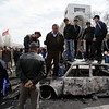 Kyrgyz men stand on a burned-out car in front of the Kyrgyz government headquarters on central square in Bishkek, Kyrgyzstan, Thursday, April 8, 2010. An opposition coalition in Kyrgyzstan said it has formed an interim government that will rule the turbulent Central Asian nation for six months. Opposition leader Roza Otunbayeva said Thursday she will head the government that dissolved the parliament and will take up legislative duties.(AP Photo/Ivan Sekretarev)
