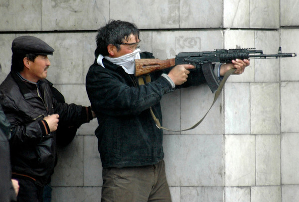 An unidenttified man fires an automatic weapon near the main government building in Bishkek, Kyrgyzstan, Wednesday, April 7, 2010. Police in Kyrgyzstan opened fire on thousands of angry protesters who tried to seize the Central Asian nation's main government building, after beating up dozens of police officers. At least four protesters were shot dead.(AP Photo/Azamat Imanaliyev)
