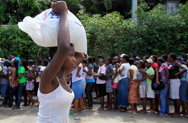 A woman walks with a bag of rice on her head as others line up at a food distribution in Port-au-Prince, Wednesday, March 24, 2010. A 7.0-magnitude earthquake hit Haiti on Jan. 12, killing and injuring thousands and leaving more than a million people living in makeshift camps.(AP Photo/Jorge Saenz)