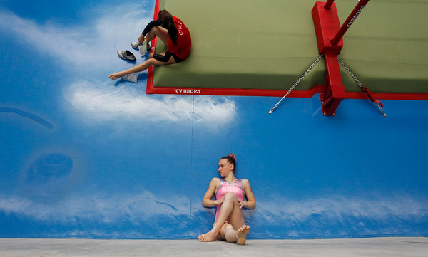 Argentina's Valeria Pereyra, bottom center, lying on the floor, stretches her legs against a wall prior to competing in the women's individual apparatus event at the South American Games in Medellin, Colombia, Wednesday, March 24, 2010. (AP Photo/Fernando Vergara)