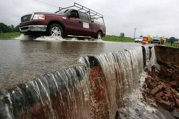 A motorist passes by a section of washed out road along U.S. Hwy. 4 between Ashland Miss., and Holy Springs Miss., Sunday, May 2, 2010. The road collapsed due to flash flooding and the Mississippi Department of Transportation spent the rest of the day to stop further erosion. (AP Photo/Northeast Mississippi Daily Journal, Thomas Wells)