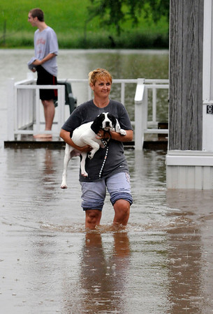 In this  May 2, 2010 photo, Sherry Wilkerson, of Bowling Green, Ky., carries her dog through high water at her mobile home as members of the Warren County Rescue Squad checked on the residents as water continued to rise in Bowling Green, Ky. (AP Photo/Bowling Green Daily News, Joe Imel)