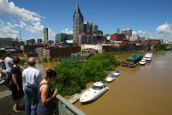 Spectators look at downtown Nashville from the Shelby Street Pedestrian Bridge over the Cumberland River on  Monday, May 3, 2010.   All of about 1, 500 guests were evacuated overnight from the Opryland Hotel, northeast of the downtown area.  The Cumberland River continues to rise at Nashville, but is nearing its crest. Floodwater has spilled onto a couple of downtown streets near the riverfront and restaurants and bars in the tourist district are closed. (AP Photo/The Tennessean, Larry McCormack)