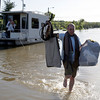 ay Krenson, right, carries clothes through floodwater belonging to his friend David Sesler, left, after recovering them from Sesler's flooded home using his houseboat  Monday, May 3, 2010, in Nashville, Tenn. After heavy weekend rains and flooding, officials in Tennessee are preparing for the Cumberland River, which winds through Nashville, to crest sometime Monday afternoon. (AP Photo/Jeff Roberson)