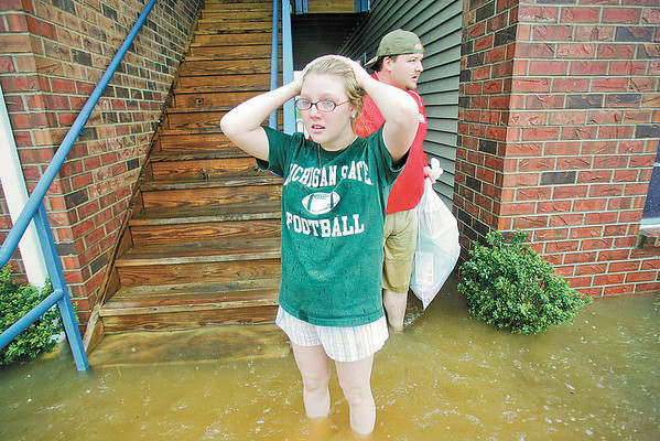 A woman leaves her flooded first floor apartment Sunday, May 2, 2010.  Friend Chris Westray helps the Craft family during the evacuation. South Central Kentucky received nearly 10 inches of rain in two days. (AP Photo/Bowling Green Daily News, Alex Slitz)