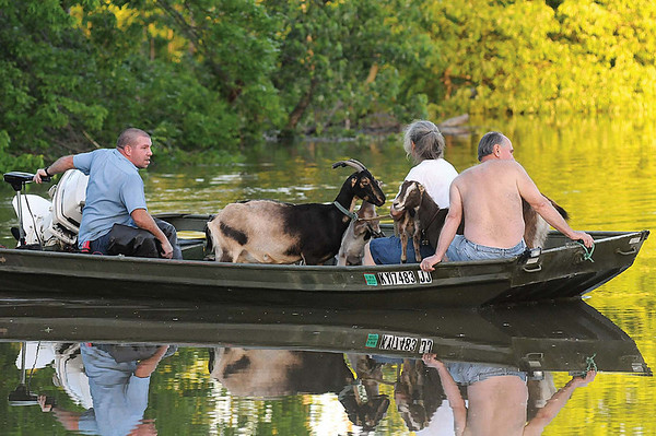 Joey Scoggins, left, guides his boat Monday evening, May 3, 2010 toward the shore of the Rowland's auto repair shop in Iuka, Ky. as he helps friends Nancy and Dale Ettinger rescue goats from their farm. Emergency declarations have been issued in 40 Kentucky counties and 15 cities, Gov. Steve Beshear said Monday afternoon.  (AP Photo/The Paducah Sun, John Wright)