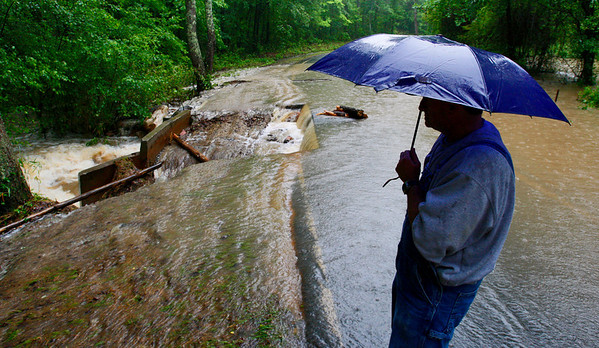 Mark Rainwater stares at the rushing water going across a roadway Monday, May 3, 2010 in Douglasville, Ga. (AP Photo/The Atlanta Journal & Constitution, John Spink)
