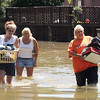 Phyllis McDonald, right, carries boxes of belongings, while Mindy Goff, left, hauls a basket full of clothing and Janie Goff follows them Monday, May 3, 2010 as they wade through flood waters in their neighborhood in Lake City, Ky. Emergency declarations have been issued in 40 Kentucky counties and 15 cities, Gov. Steve Beshear said Monday afternoon.  (AP Photo/The Paducah Sun, John Wright)