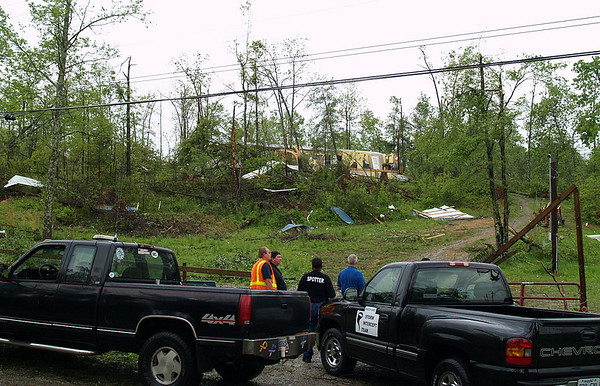Bystanders survey a path of broken tree limbs and debris that lead up to a damaged trailer home on  May 2, 2010 in Mannington, Ky.  A tornado damaged at least two trailer homes in Crofton, Ky. and uprooted several trees early Sunday morning.   (AP Photo/Kentucky New Era, Kevin Hoffman)