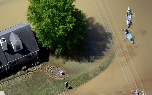 People paddle canoes down a street in Nashville, Tenn., on Monday, May 3, 2010. After heavy weekend rains and flooding, officials in Tennessee are preparing for the Cumberland River, which winds through Nashville, to crest more than 11 feet Monday afternoon.  (AP Photo/Mark Humphrey)