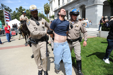"""TMartin Francis Brown, 45, is arrested at a tea party rally at the Capitol in Sacramento, Calif. on Thursday, April 15, 2010.  """"Give me my freedom,"""" he yelled on stage as a speaker was addressing the crowd. Officers Rick Turner, left and Jeff Lane said they """"arrested him for demonstration without a permit and resisting arrest."""" (AP Photo/The Sacramento Bee, Hector Amezcua)"""