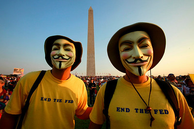 """Two men who asked to be called only, """"Guy Fawkes,"""" attend a tea party rally by the Washington Monument in Washington, on Thursday, April 15, 2010. """"We will reveal our true identities when the federal reserve reveals who they are owned by,"""" they said, """"we are defenders of honest money."""" (AP Photo/Jacquelyn Martin)"""