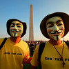 "Two men who asked to be called only, ""Guy Fawkes,"" attend a tea party rally by the Washington Monument in Washington, on Thursday, April 15, 2010. ""We will reveal our true identities when the federal reserve reveals who they are owned by,"" they said, ""we are defenders of honest money."" (AP Photo/Jacquelyn Martin)"
