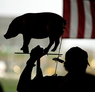 A man holds a pig representing government spending as he attends a tea party tax rally Thursday, April 15, 2010, in Kansas City, Kan. (AP Photo/Charlie Riedel)