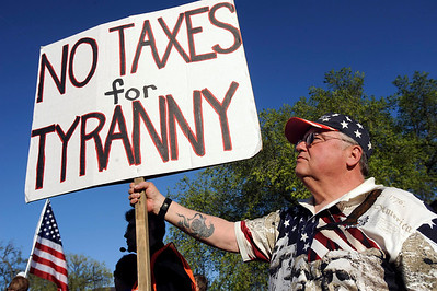 John Panasuk of New London, Minn. held a sign during the tea party rally at the Minnesota state capitol in St Paul, Minn., Thursday, April 15, 2010. More than 500 people attended the rally. (AP Photo/Craig Lassig)