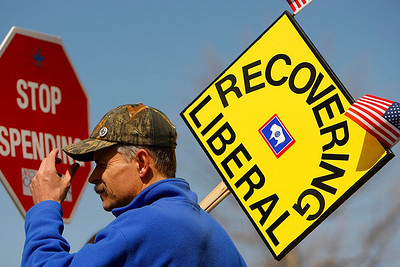 Kevin Wadsworth holds a 'Recovering Leberal' sign during a 'Tea Party' at Conwell Park on Thursday, April 15, 2010, in Casper, Wyo. (AP Photo/Casper Star-Tribune, Dan Cepeda)