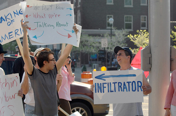 Ben Haney, left, a student at the University of Southern Indiana, holds up a sign criticizing the tea party as tea party supporter Kevin Harrison of Evansville, points out the small group during a rally in Evansville, Ind. on Thursday, April 15, 2010. Several local citizens and politicians addressed the crowd about taxation, government spending and health care. (AP Photo/The Evansville Courier & Press, Jason Clark)