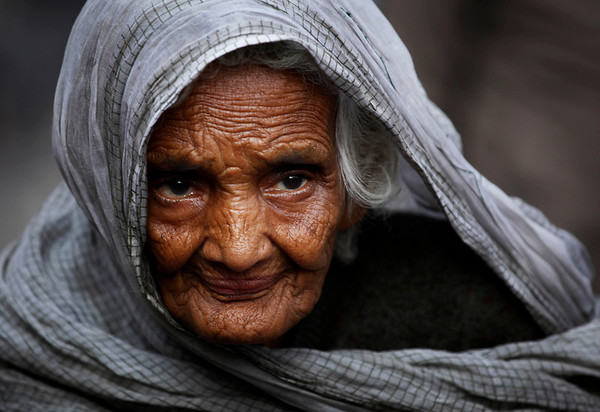 An elderly woman begs for alms on a roadside in the old part of New Delhi, India, Wednesday, Feb. 3, 2010. (AP Photo/Rajesh Kumar Singh)