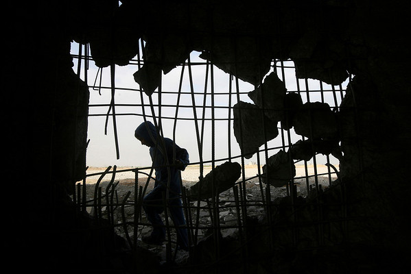 A Palestinian youth walks through the rubble following an Israeli air strike in the southern Gaza Strip, Wednesday, Feb. 3, 2010. Early Wednesday, Israeli warplanes struck two smuggling tunnels under the Gaza-Egypt border in response to the barrel bombs and the firing of a rocket from Gaza, the military said. Such airstrikes are automatic reactions to militant attacks. (AP Photo/Eyad Baba)