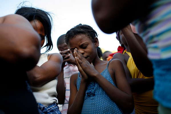 APTOPIX_Haiti_Earthquake_PA.JPG A girl pray among believers during a religious service in Port-au-Prince, Monday, Feb. 1, 2010. A 7.0-magnitude earthquake hit Haiti on Jan. 12 leaving thousands dead and many displaced. (AP Photo/Rodrigo Abd)