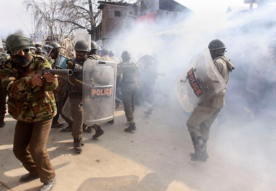 APTOPIX_India_Kashmir_Prote.JPG An Indian police officer, left, prepares to fire tear a gas shell as Indian paramilitary soldiers run for cover from shells thrown back at them by Kashmiri Muslim protesters, unseen, during a protest in Srinagar, India, Monday, Feb. 1, 2010. Rock-throwing protesters clashed with government forces in Indian-controlled Kashmir on Monday, a day after a police-fired tear gas shell struck and killed a boy. (AP Photo/ Dar Yasin)