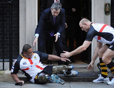 APTOPIX_BRITAIN_LON803.JPG British Prime Minister Gordon Brown, centre back, and rugby player Lawrence Dellaglio, right, rush to assist double amputee Derek Derenalagi as he falls on the doorstep of 10 Downing Street, London, Monday Feb. 1, 2010.  The former soldier Derenalagi, who lost both legs in Afghanistan in 2007,  was visiting the Prime Minister to promote a St George's Day Rugby Match to raise money for the Help For Heroes charity.  Dellaglio is a former England rugby team captain. (AP Photo/Stefan Rousseau, PA) ** UNITED KINGDOM OUT - NO SALES - NO ARCHIVES **