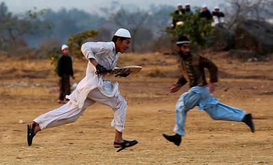 APTOPIX_PAKISTAN_DAILY_LIFE.JPG Tow Pakistanis run while playing cricket in a field on the outskirts of Islamabad, Pakistan, Monday, Feb. 1, 2010. (AP Photo/Muhammed Muheisen)
