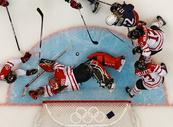 Canada goalie Shannon Szabados (1) blocks a shot against USA in the second period of the women's gold medal ice hockey game at the Vancouver 2010 Olympics in Vancouver, British Columbia, Thursday, Feb. 25, 2010.  Around Szabados are Canada's Catherine Ward (18), Caroline Ouellette (13), Meaghan Mikkelson, and USA's Jenny Potter, top. (AP Photo/Julie Jacobson)