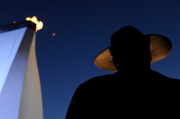 A Royal Canadian Mounted Police officer stands next to an Olympic flame ahead of the evening's medal presentations at the Vancouver 2010 Olympics in Whistler, British Columbia, Sunday, Feb. 14, 2010.  (AP Photo/Gero Breloer)