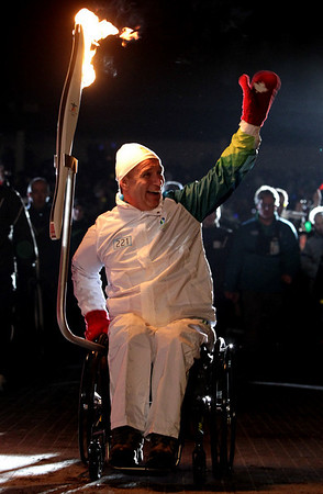 Six-time Parlaympic medalist Rick Hansen, of Canada, carries the Olympic flame during the Olympic torch relay in Richmond, British Columbia, Canada  on Tuesday Feb. 9, 2010. The Olympic flame is on a 106 day journey across Canada in the longest domestic torch relay in Olympic history. It will end with the lighting of the Olympic cauldron at the opening ceremonies for the Vancouver Winter Olympics on Feb.  12.  (AP Photo/The Canadian Press,Darryl Dyck)