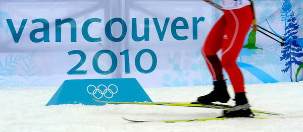 A Biathlete skates past a 'Vancouver 2010' sign during a training session at the Biathlon track at the Vancouver 2010 Olympics in Whistler, British Columbia, Friday, Feb. 12, 2010. (AP Photo/Jens Meyer)