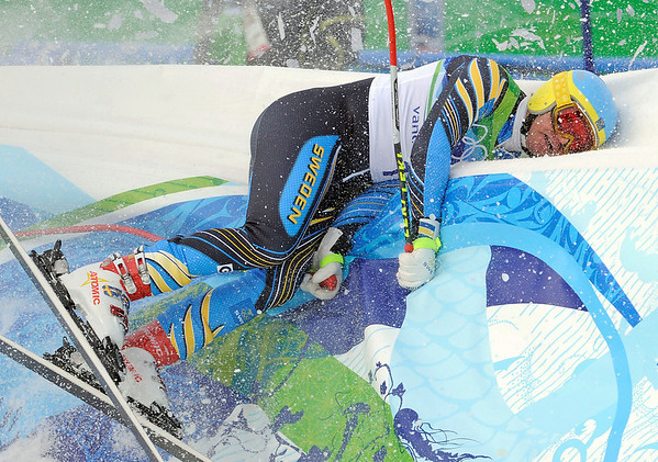 Sweden's Patrik Jaerbyn crashes into the safety fencing in the finish area after completing the Men's downhill at the Vancouver 2010 Olympics in Whistler, British Columbia, Monday, Feb. 15, 2010. (AP Photo/Gero Breloer)