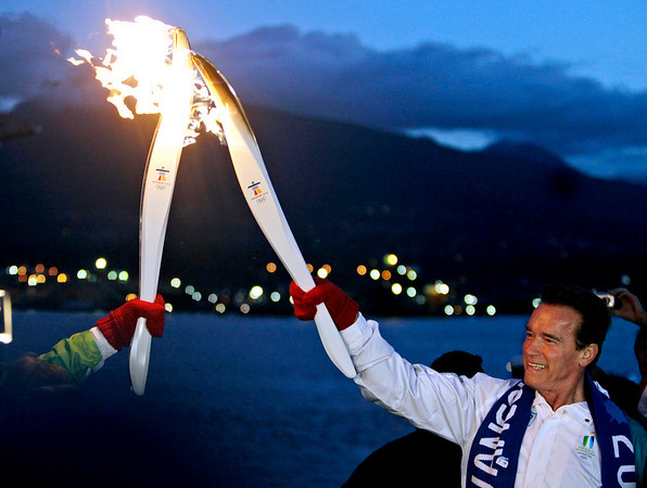 California Gov. Arnold Schwarzenegger hands off the Olympic torch to a fellow runner at the Vancouver 2010 Olympics in Vancouver, British Columbia, early Friday, Feb. 12, 2010. (AP Photo/Marcio Sanchez)