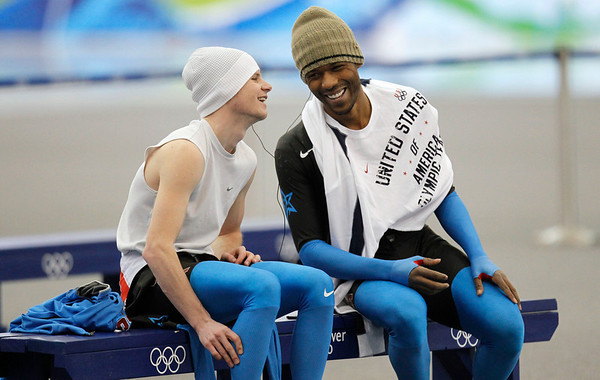 American speed skaters Shani Davis, right, and Tucker Fredricks, left, share the earphones of a walkman prior to  training at the Richmond Olympic Oval at the Vancouver 2010 Olympics in Vancouver, British Columbia, Thursday, Feb. 11, 2010. (AP Photo/Kevin Frayer)