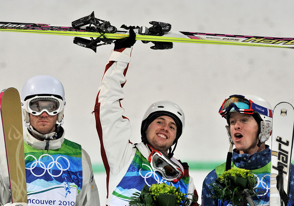 Alexandre Bilodeau of Canada, center  celebrates becoming Olympic moguls champion nest to runner up Dale Begg-Smith of Australia, left and Bryon Wilson of the USA, right at the Vancouver 2010 Olympics in Vancouver, British Columbia, Sunday, Feb. 14, 2010. (AP Photo/Bela Szandelszky)