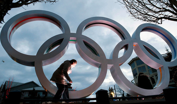 Canadian immigrant Mina Bahmanyar, originally from Iran, clambers into a set of Olympic rings so that her family can photograph her on a plaza at the Vancouver 2010 Olympics in Whistler, British Columbia, Tuesday, Feb. 9, 2010. (AP Photo/Elaine Thompson)