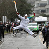Torchbearer Michael Tchao jump as he carries the Olympic flame during the Olympic torch relay at Simon Fraser University in Burnaby, British Columbia, on Thursday, Feb. 11, 2010. The Olympic flame is on a 106-day journey across Canada in the longest domestic torch relay in Olympic history. It will end with the lighting of the Olympic cauldron at the opening ceremonies for the Vancouver Winter Olympics on Friday, Feb. 12. (AP Photo/The Canadian Press, Darryl Dyck)