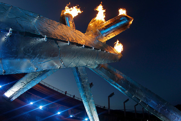 Pedestrians walk past the Olympic flame at the Vancouver 2010 Olympics in Vancouver, British Columbia, Sunday, Feb. 14, 2010. (AP Photo/Marcio Sanchez)