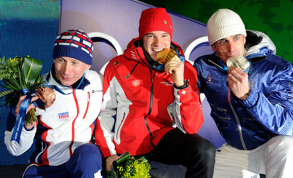 Lukas Bauer of the Czech Republic, bronze medal winner, Dario Cologna of Switzerland, gold medal winner and Pietro Piller Cottrer of Italy , silver medal winner, from left to right, pose with their medals during the medal ceremony for the men's cross-country skiing 15km freestyle competition at the Vancouver 2010 Olympics in Whistler, British Columbia, Monday, Feb. 15, 2010. (AP Photo/Jens Meyer)