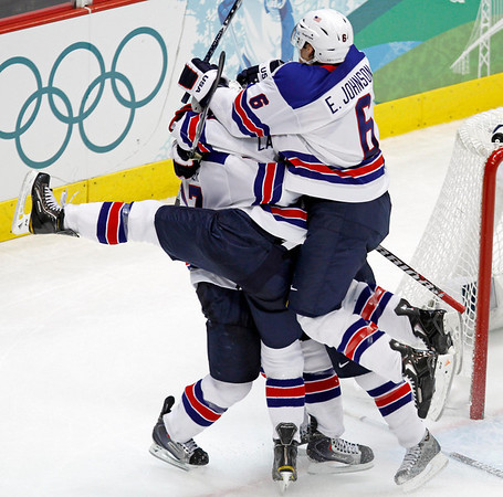 Players swarm USA's Ryan Kesler to celebrate his open net goal  during the third period of a preliminary round men's ice hockey game against Canada at the Vancouver 2010 Olympics in Vancouver, British Columbia, Sunday, Feb. 21, 2010. USA won 5-3. (AP Photo/Gene Puskar)