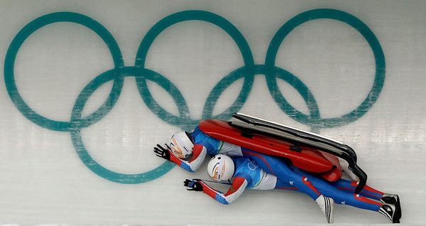 Vladislav Juzhakov, right, and Vladimir Machnutin of Russia crash during a run of the men's doubles luge training at the Vancouver 2010 Olympics in Whistler, British Columbia, Monday, Feb. 15, 2010. (AP Photo/Michael Sohn)